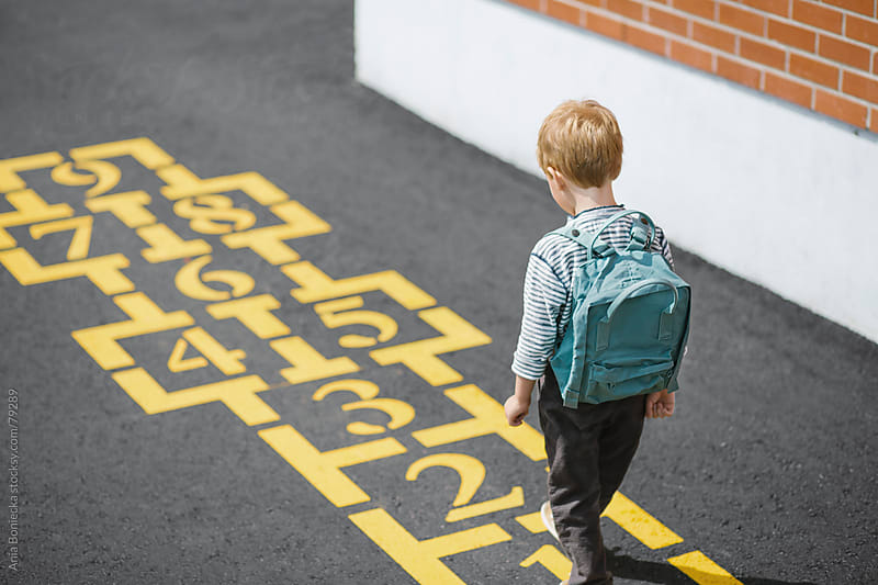 A boy walking up to a hopscotch game at a school playground by Ania Boniecka for Stocksy United