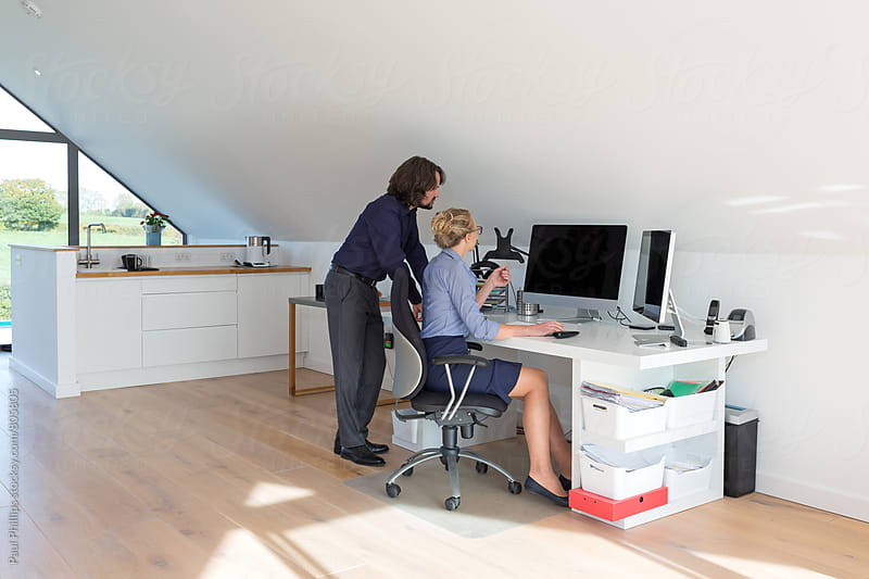 Couple working in their modern home office by Paul Phillips for Stocksy United