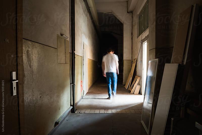 Man walking down dark corridor by Urs Siedentop & Co for Stocksy United