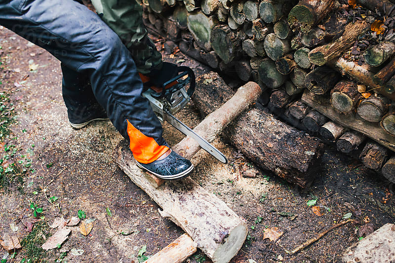 lumberjack chopping wood in a forest with an electric saw by Ivo de Bruijn for Stocksy United