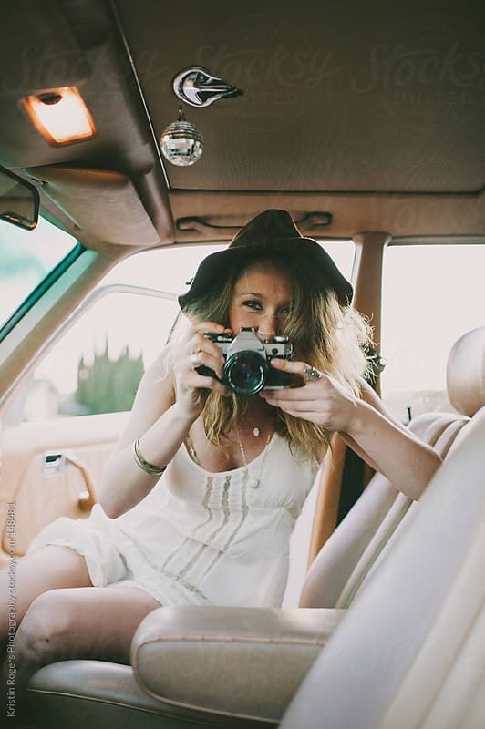 Pretty stylish girl playing with camera inside of old car by Kristin Rogers Photography for Stocksy United