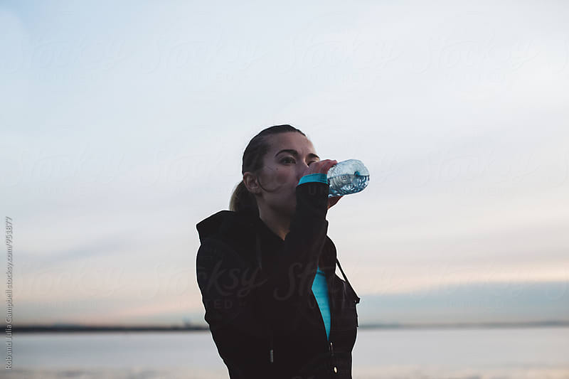 Young, healthy caucasian woman drinking water outside after running workout by Rob and Julia Campbell for Stocksy United