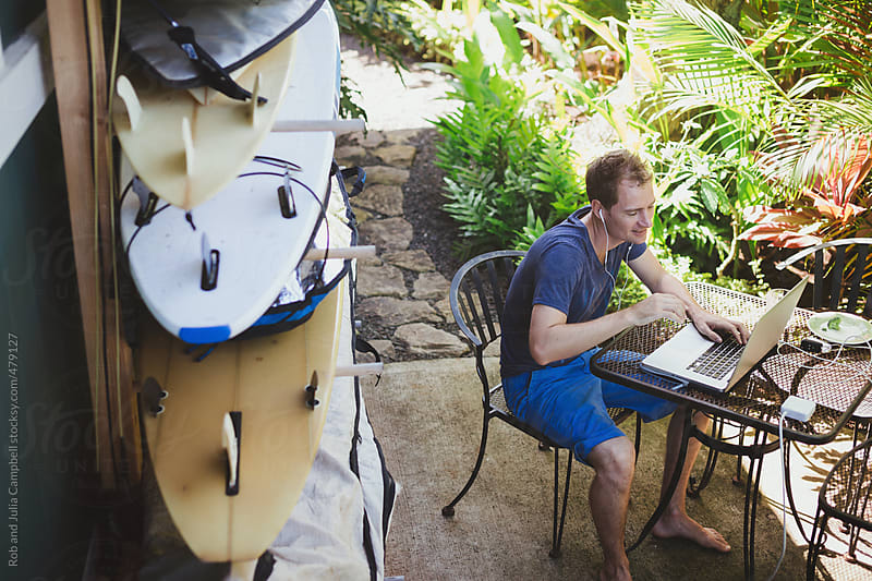 Content man working on laptop in tropical yard with surfboards in background by Rob and Julia Campbell for Stocksy United