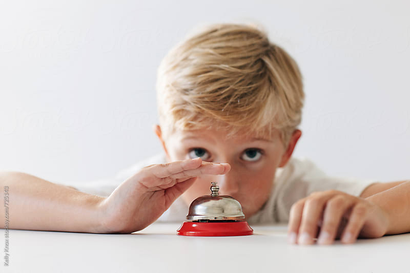 impatient boy rings a counter bell by Kelly Knox for Stocksy United