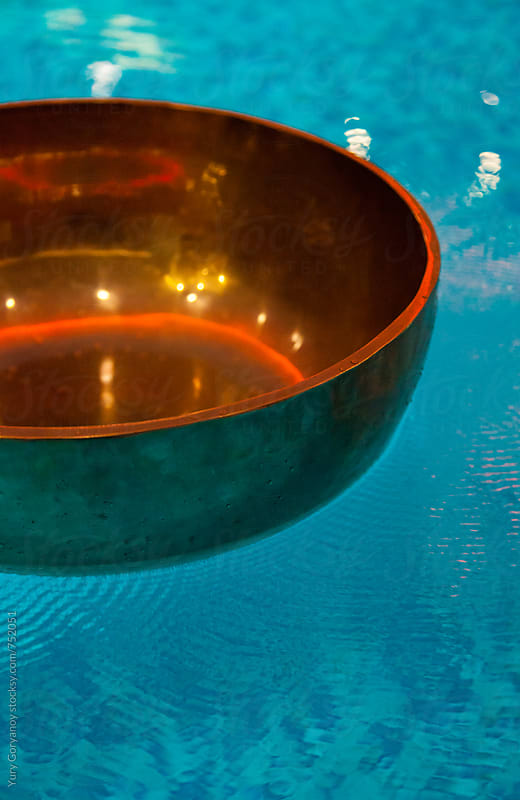 Resonating Tibetan bowl of water by Yury Goryanoy for Stocksy United
