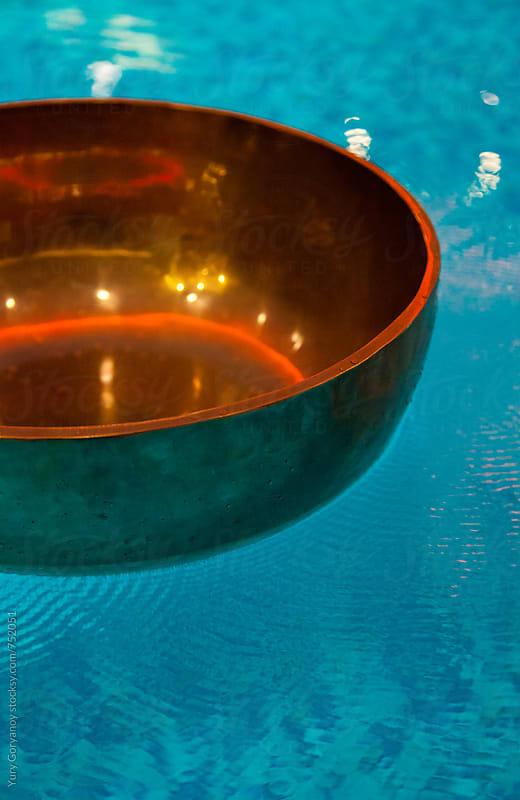 Resonating Tibetan bowl of water by Юрий Горяной for Stocksy United