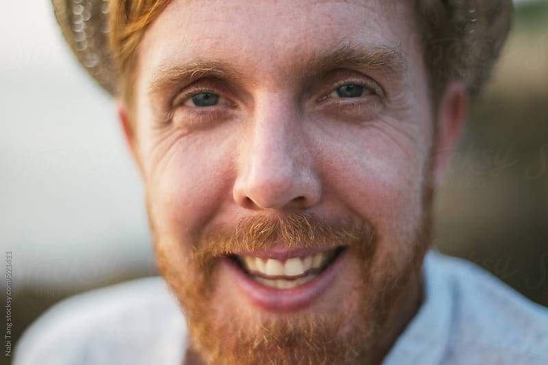 Close up shot of a smiling ginger guy by Nabi Tang for Stocksy United