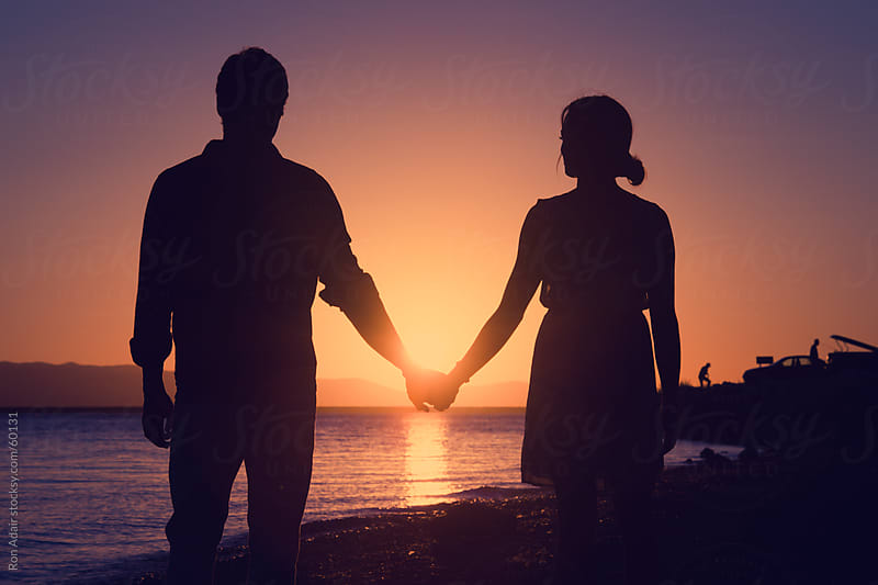 Love: Young couple in love holding hands by Ron Adair for Stocksy United