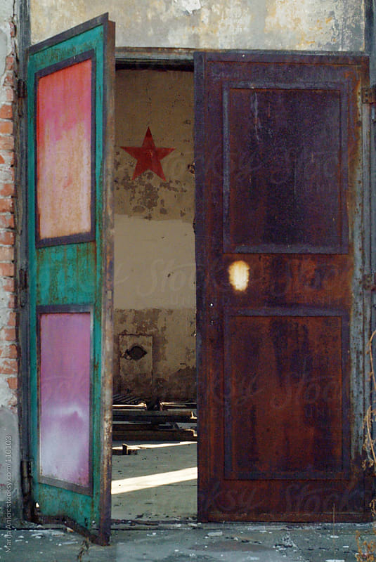 slightly open old rusty colorful door by Marija Anicic for Stocksy United