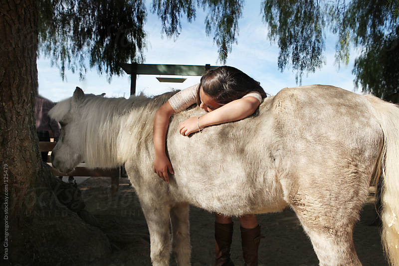 Young Girl Laying on Horse by Dina Giangregorio for Stocksy United