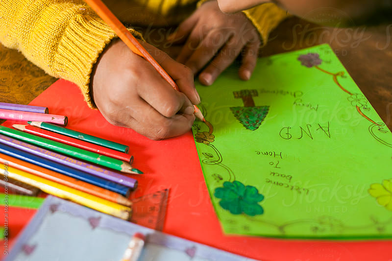 Close up of a young sister making a Christmas card for her brother who is coming home soon. by Shikhar Bhattarai for Stocksy United