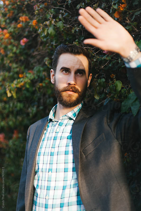 Young Male with a Beard Covers His Eyes from Sun by Caleb Thal for Stocksy United