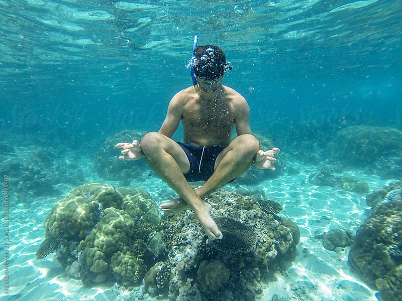 Young man snorkeling doing yoga position underwater by Alejandro Moreno de Carlos for Stocksy United