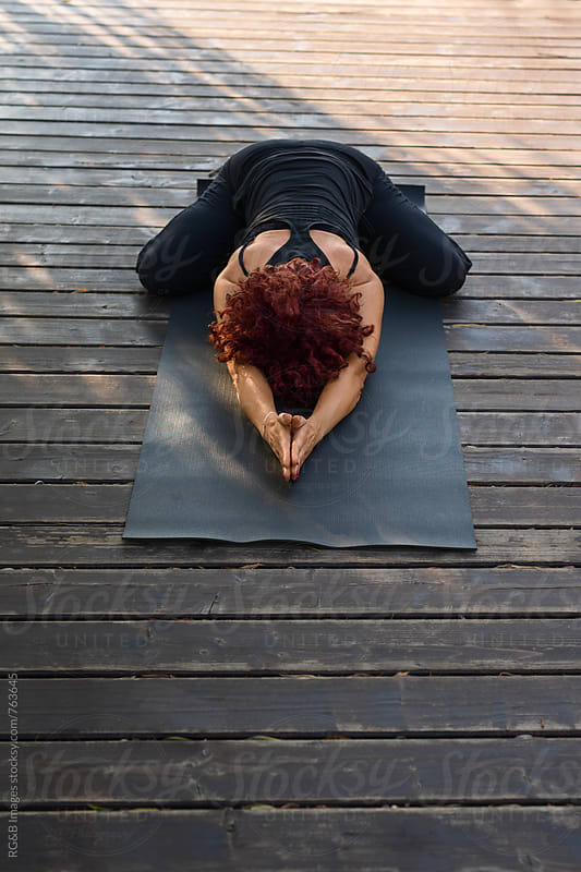 Woman practicing yoga and meditation on a wooden deck by RG&B Images for Stocksy United