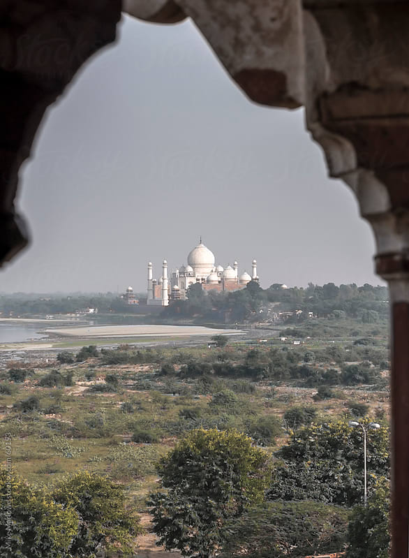 The Taj Mahal shot from a distance and framed by stone trellis work. by Mike Marlowe for Stocksy United
