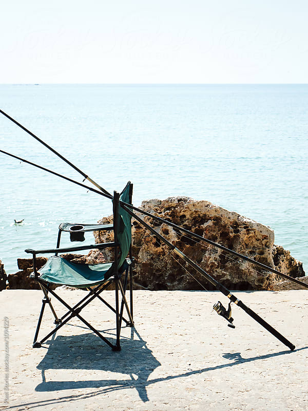 Empty fishing chair and rods by Pixel Stories for Stocksy United