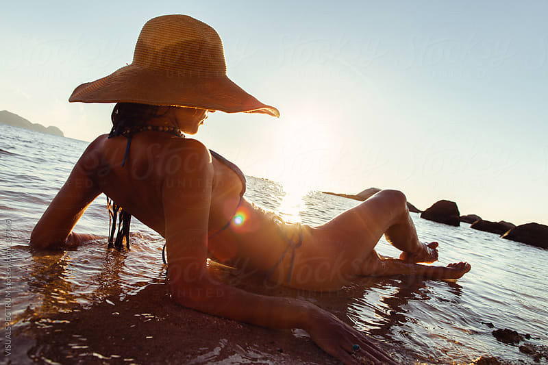 Pretty Woman Tanning on Beach by VISUALSPECTRUM for Stocksy United