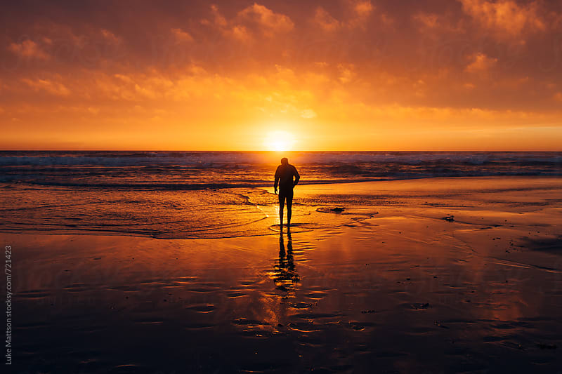 A Young Man Stands On The Shore As The Sun Sets Over The Pacific Ocean by Luke Mattson for Stocksy United