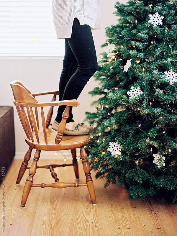 Young woman decorating Christmas tree by Daniel Kim Photography for Stocksy United