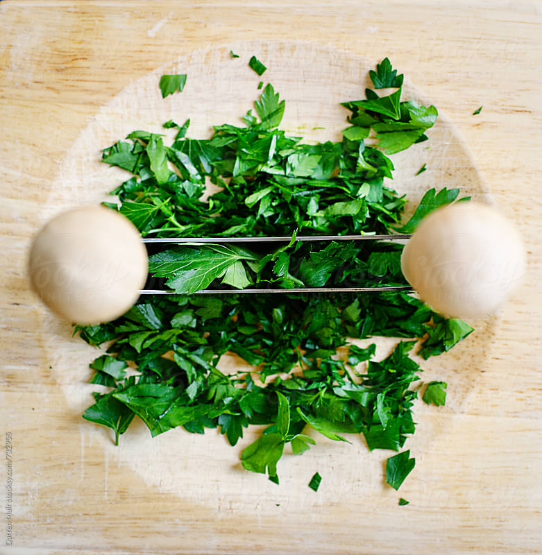 Chopping parsley in a herb cutter.  by Darren Muir for Stocksy United