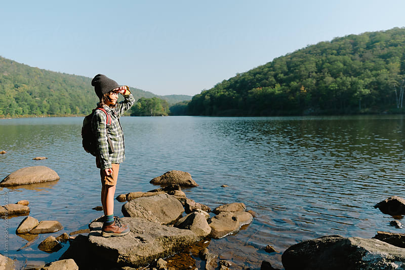 Young boy at lake looks into the distance by kelli kim for Stocksy United