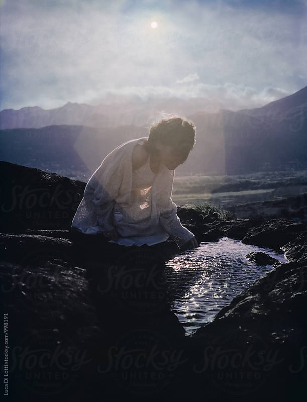 young beautiful woman sitting on a rock on a mountain by Luca Di Lotti for Stocksy United