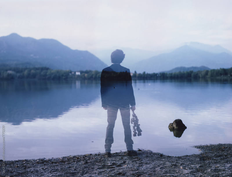 Double-exposure on Polaroid Film of a young man holding dried flowers by a lake  by Luca Di Lotti for Stocksy United