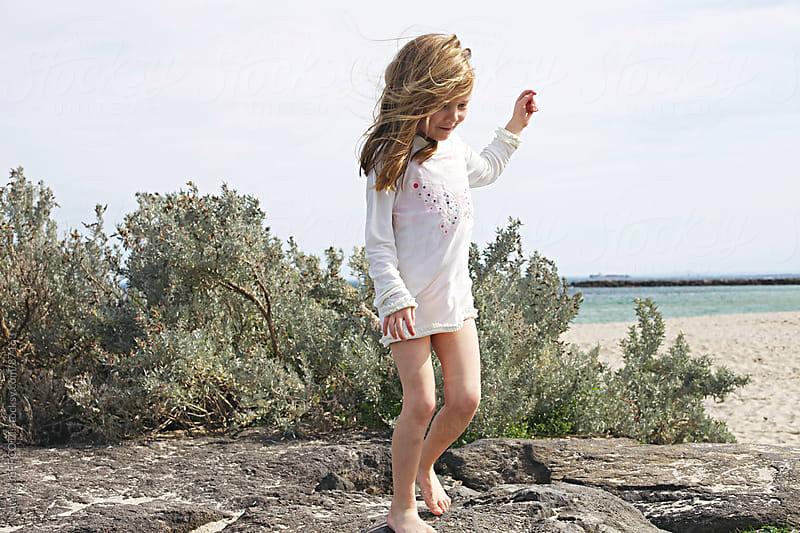 girl walking along rocks by Natalie JEFFCOTT for Stocksy United