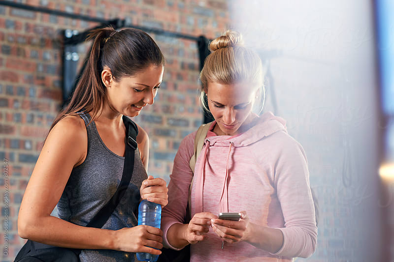 Fitness women with water bottle and cell phone  by Daxiao Productions for Stocksy United