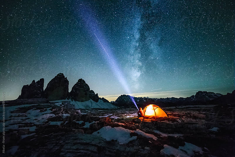 male adventurer with strong headlamp sitting beside illuminated red orange under the milky way at the three peaks by Leander Nardin for Stocksy United