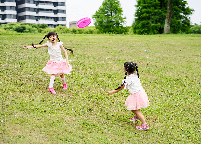 Two cheerful kids playing frisbee by Lawren Lu for Stocksy United