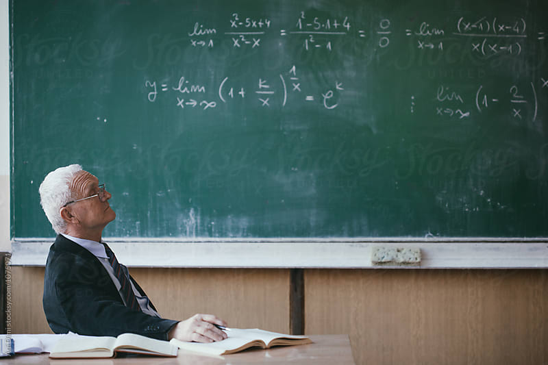 Portrait of a mature professor in a classroom by Ani Dimi for Stocksy United