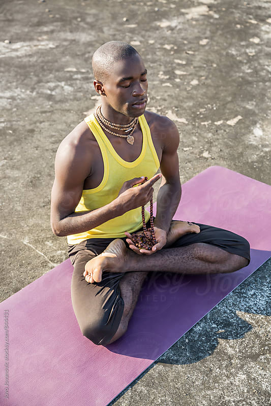 Vertical view of a handsome fit man meditating in a lotus pose  by Jovo Jovanovic for Stocksy United