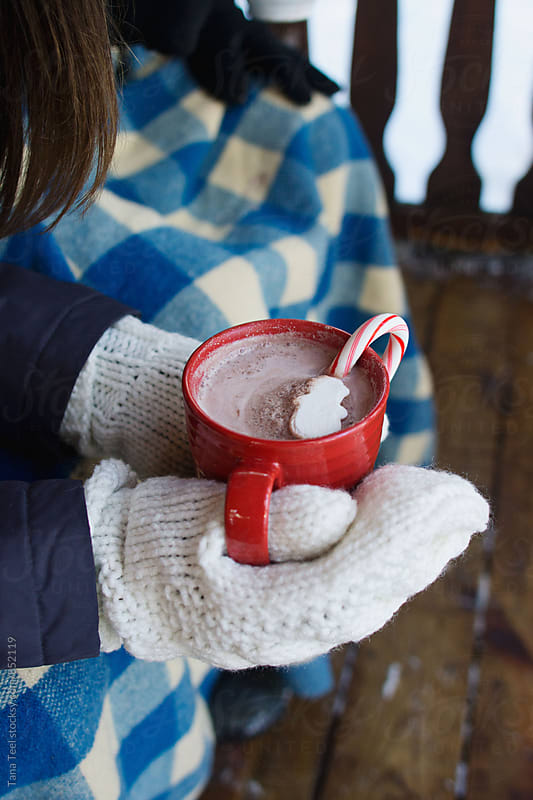 person holding cup of cocoa outside on porch by Tana Teel for Stocksy United