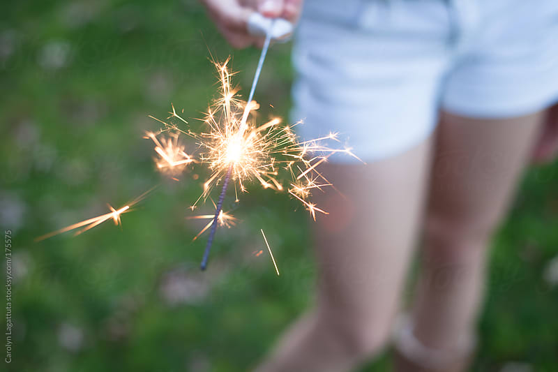 Girl in white shorts holding a sparkler  by Carolyn Lagattuta for Stocksy United