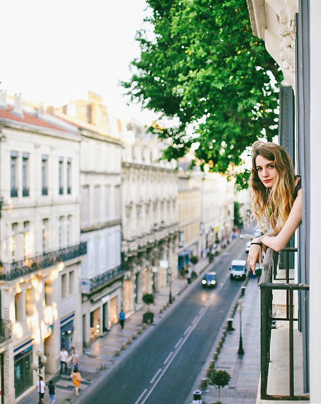 Young woman leaning out the window by Giulia Squillace for Stocksy United