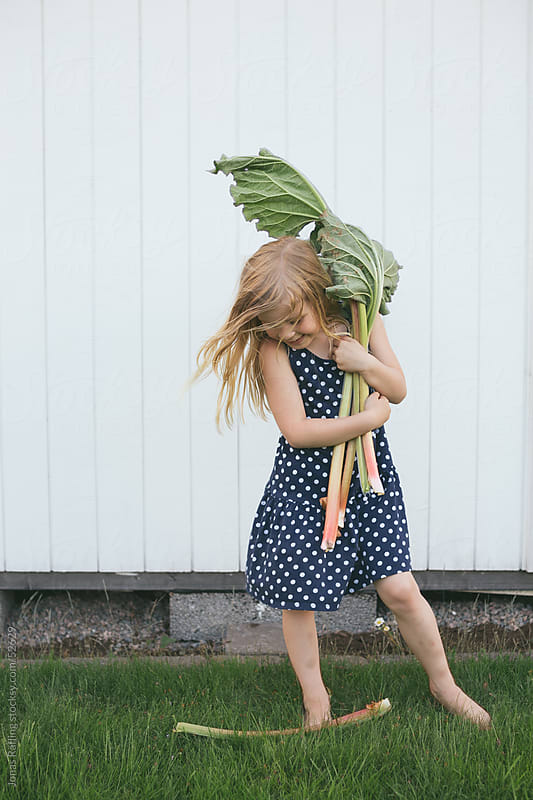 Barefoot girl in dotted dress holding rhubarb in her hands by Jonas Räfling for Stocksy United