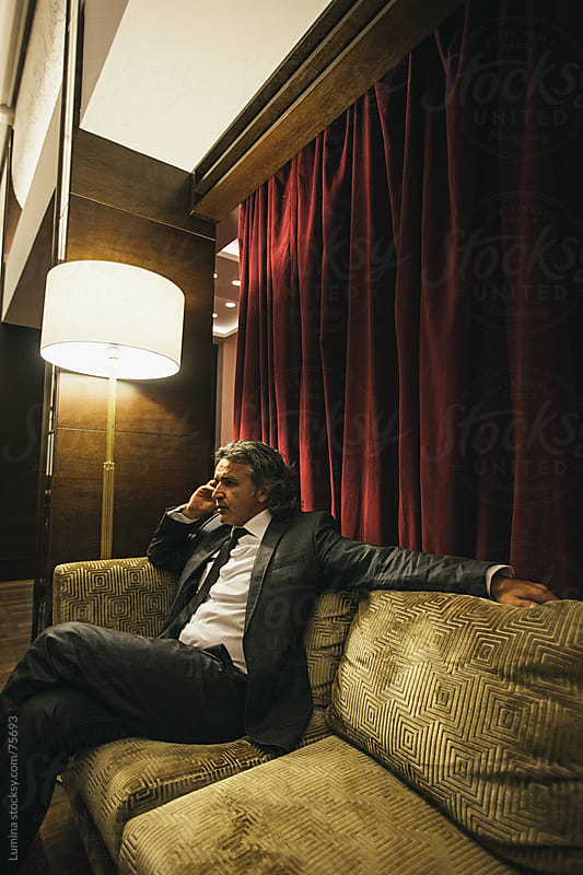 Businessman Telephoning in a Hotel Lobby by Lumina for Stocksy United