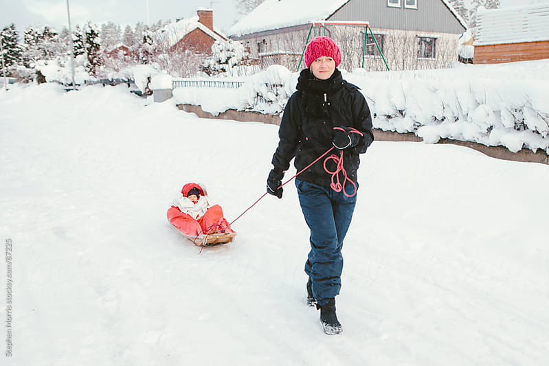 Mother Pulls Sleeping Baby in Sled in the Snow by Stephen Morris for Stocksy United