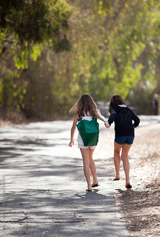 Best friends skipping down a path and holding hands by Carolyn Lagattuta for Stocksy United