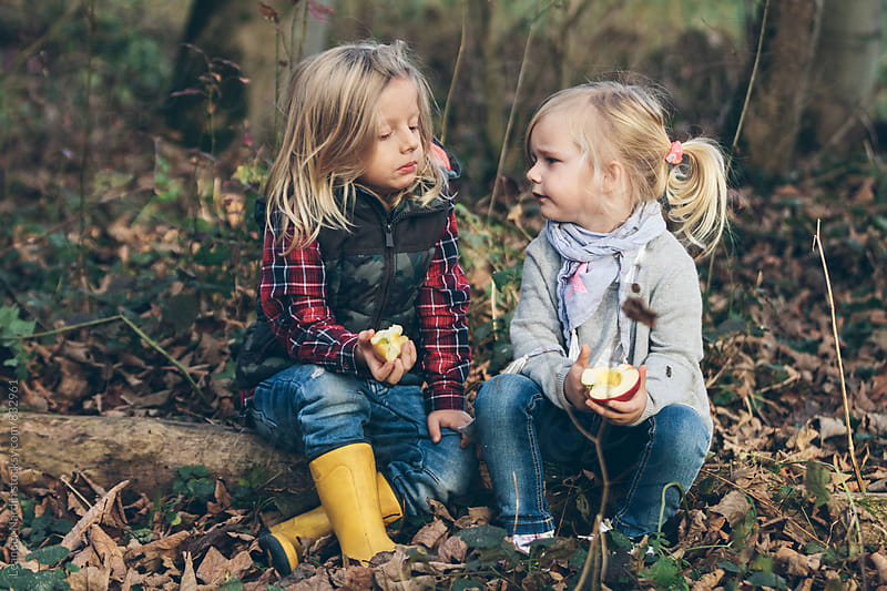 little boy and girl sitting on forest ground eating an apple by Leander Nardin for Stocksy United