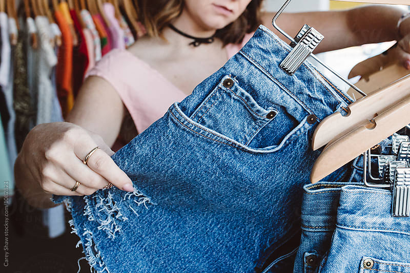 Young woman shopping for denim cut-offs in cute retail shop by Carey Shaw for Stocksy United