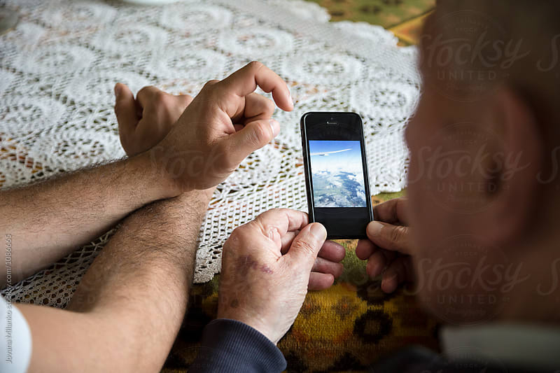 Grandson showing to his grandfather his travel photos by Jovana Milanko for Stocksy United