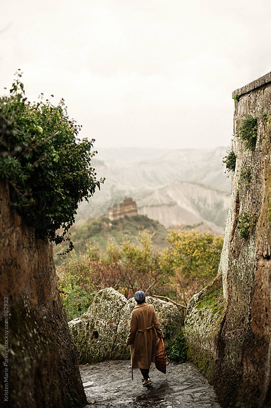 Woman walking through stone Italian village in Tuscany with basket by Kristen Marie Parker for Stocksy United