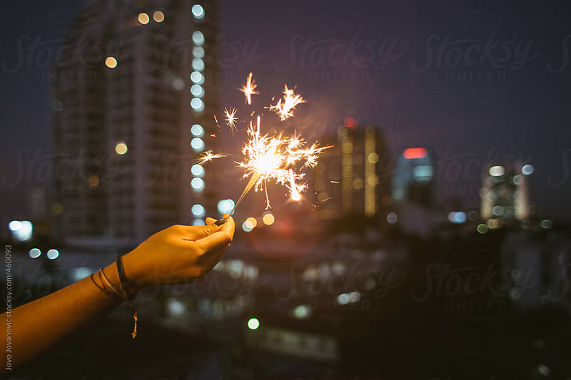 Hand holding sparkler in a metropolitan city at night by Jovo Jovanovic for Stocksy United