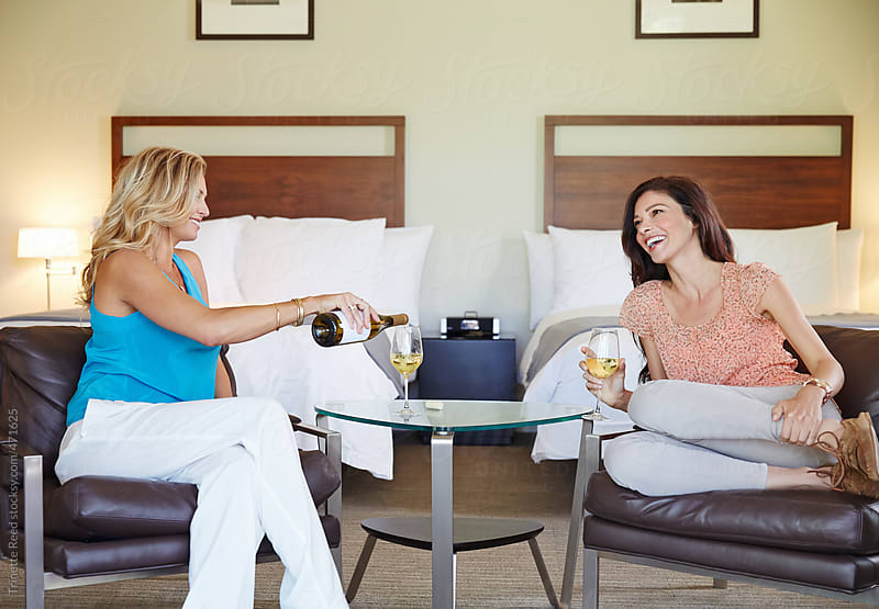 Girlfriends relaxing with wine in luxury hotel room.  by Trinette Reed for Stocksy United