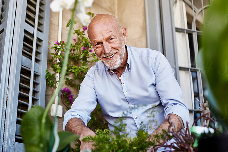 Smiling Senior Man Gardening On Balcony by ALTO IMAGES for Stocksy United