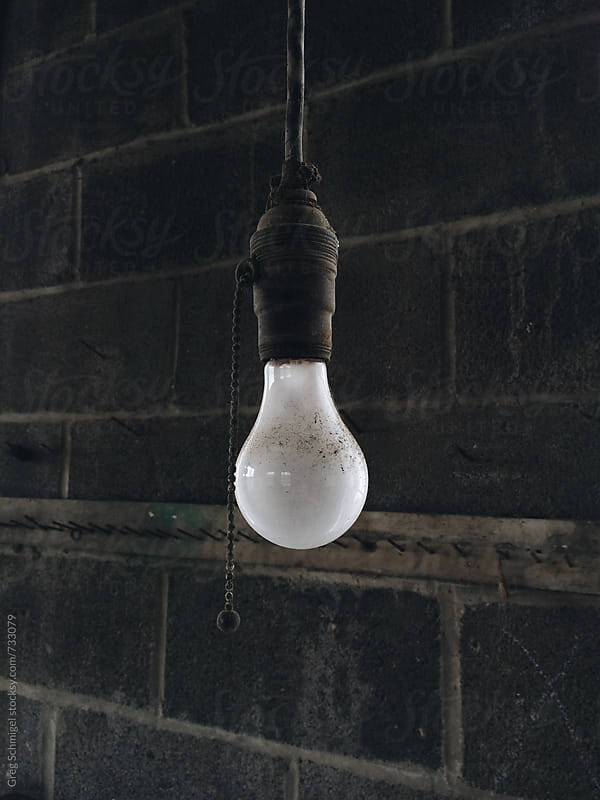 Sincle light bulb hanging from a ceiling in an abandoned garage by Greg Schmigel for Stocksy United