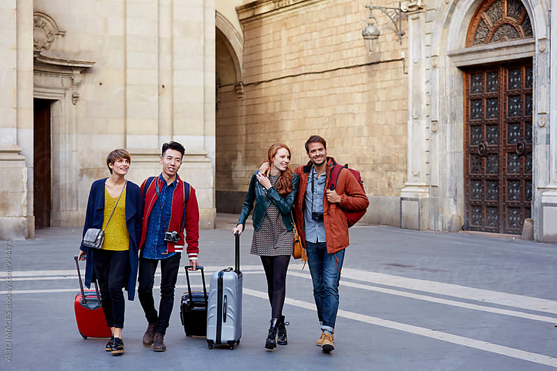 Happy Friends With Luggage Walking In City by ALTO IMAGES for Stocksy United