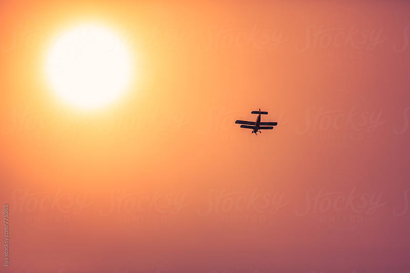 Small airplane flying in the sunset with sun in haze by Ilya for Stocksy United